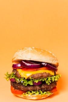 黄色の背景にコピースペースを持つハンバーガー