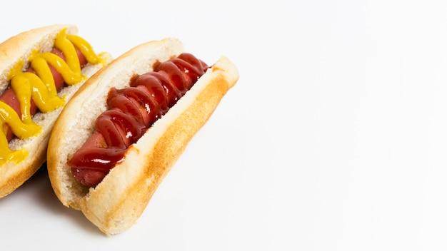 白いテーブルに調味料とホットドッグ