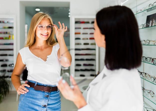 Женщина пытается очки кадр в магазине