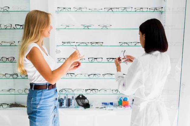 眼鏡フレームを保持している女性のミディアムショット