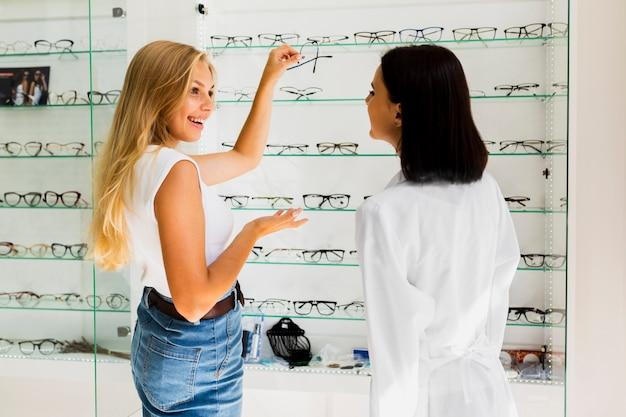 ショップでメガネフレームを保持している女性