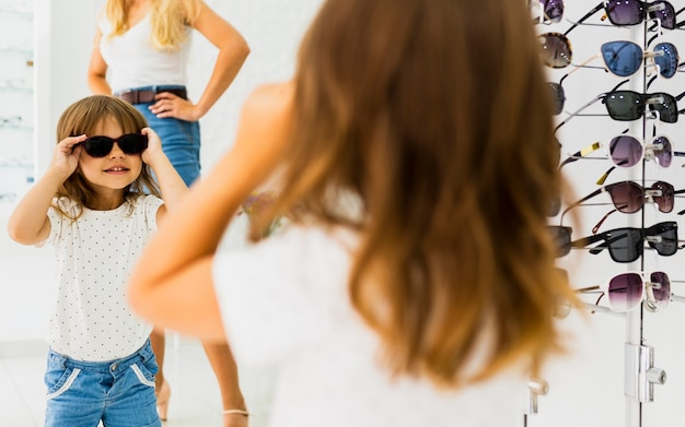 Девушка в темных очках и смотрит в зеркало
