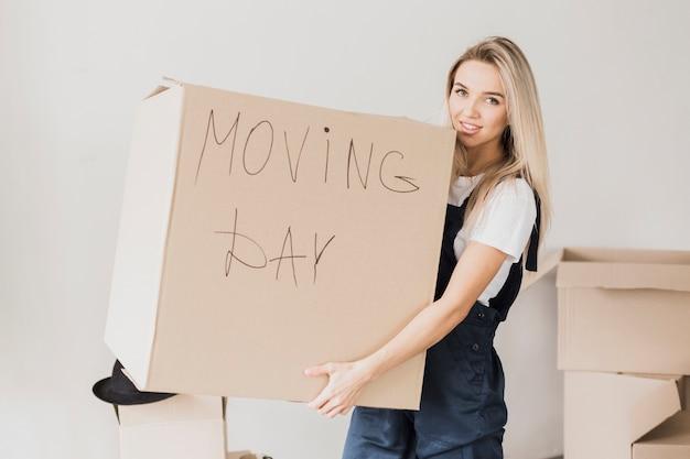 Довольно блондинка женщина, держащая картонную коробку