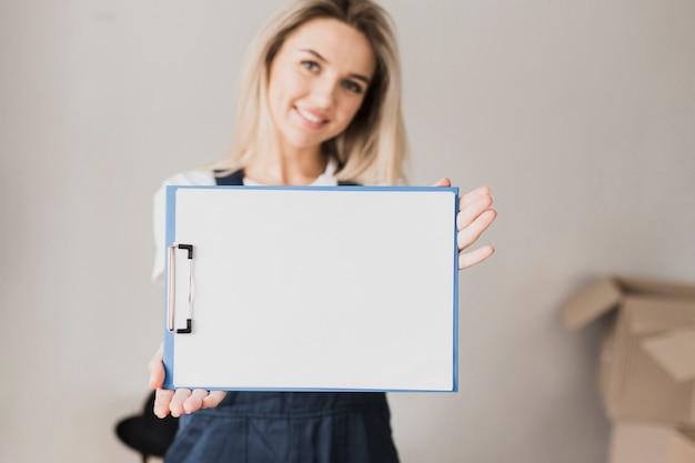 モックアップで紙のクリップボードを保持している女性
