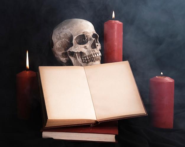 本のモックアップとキャンドルの頭蓋骨