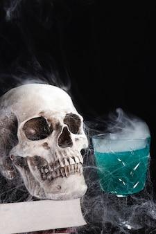緑の飲み物と人間の頭蓋骨
