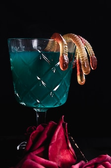 Зеленый напиток с желейными червями и розами