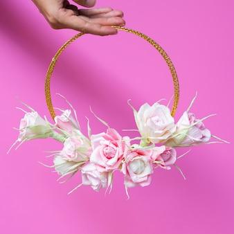 ピンクの背景に花のフレームを保持しているフロントビュー女性