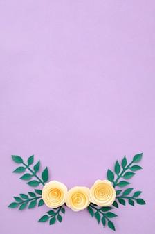 平らな紙の花と紫色の背景に葉を置く