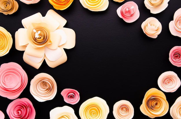 Вид сверху черный фон с рамкой милые бумажные цветы
