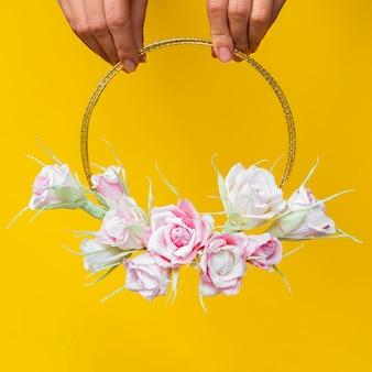 黄色の背景に花のフレームを保持している女性