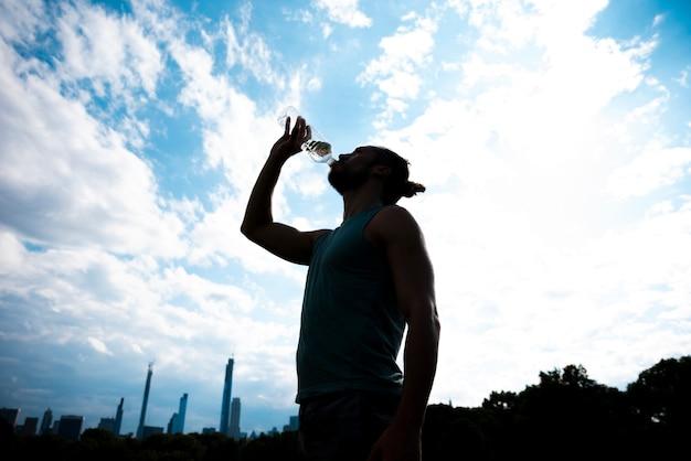 ランナーは、空を背景に水を飲む