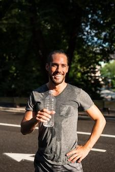 水のボトルを保持している笑顔のランナー