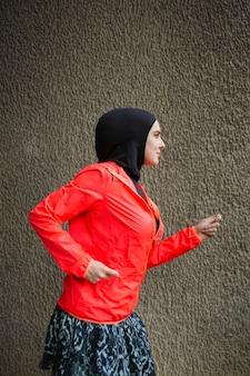 赤いジャケットを持つ女性の側面図