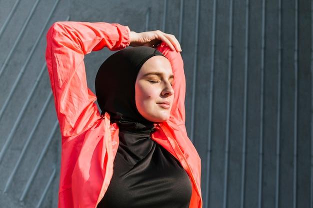 赤いジャケットのストレッチを持つ女性の正面図