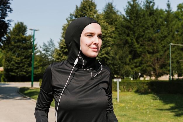 ヘッドフォンを持つ女性のミディアムショット