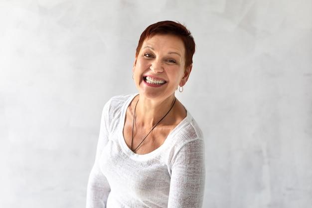 Зрелая женщина с короткими волосами, улыбаясь