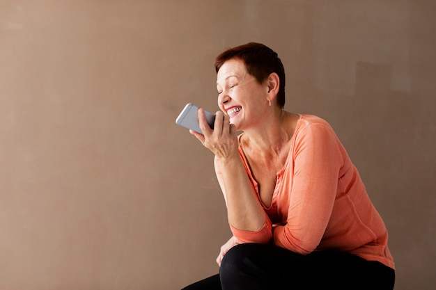 Счастливая старшая женщина с усмехаться телефона