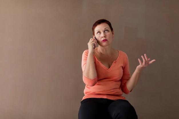 電話で真剣に話している熟女