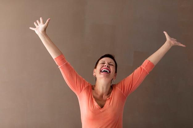 幸せな年配の女性が手を上げる