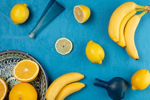 Чаша из лимонов и бананов на синем фоне