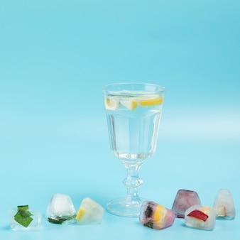 Стакан воды с лимоном с кубиками льда на синем фоне