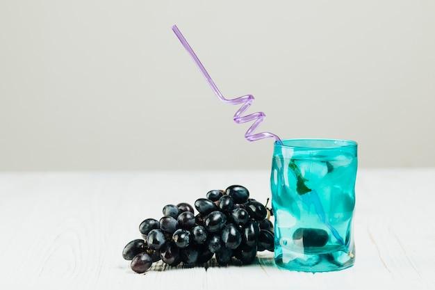 Стакан воды и винограда на простой фон
