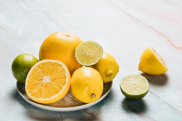 大理石の背景にレモンとプレートの高角