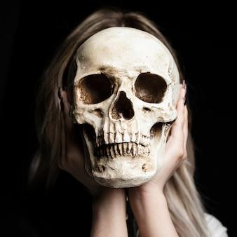 黒の背景を持つ人間の頭蓋骨を保持している女性