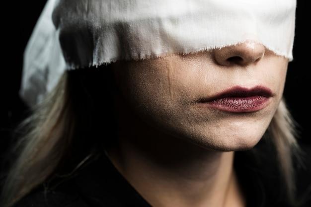 Крупный план женщины с белой завязанными глазами