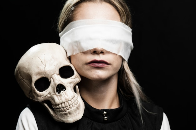 Женщина с завязанными глазами и черепом