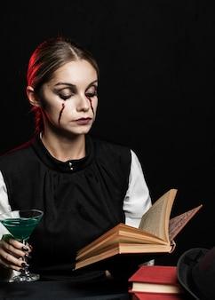 本を読んで緑の飲み物を持つ女性
