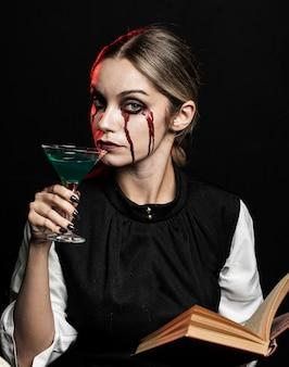 緑の飲み物と本を持つ女性