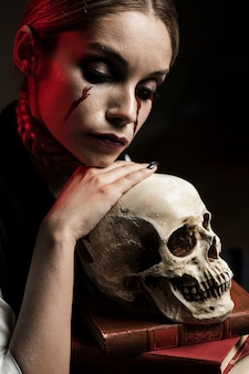 人間の頭蓋骨と本を持つ女性