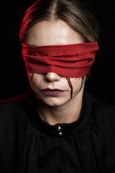 赤い目隠しを持つ女性の正面図