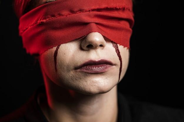 赤い目隠しを持つ女性のクローズアップ