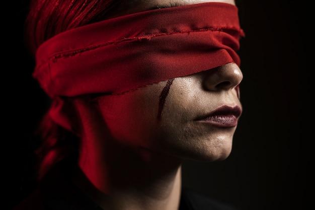 赤い目隠しを持つ女性の側面図