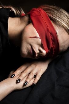 彼女の頭に横たわっている目隠しを持つ女性