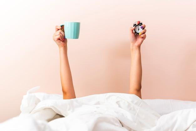 カップと時計を保持している女性の手の正面図
