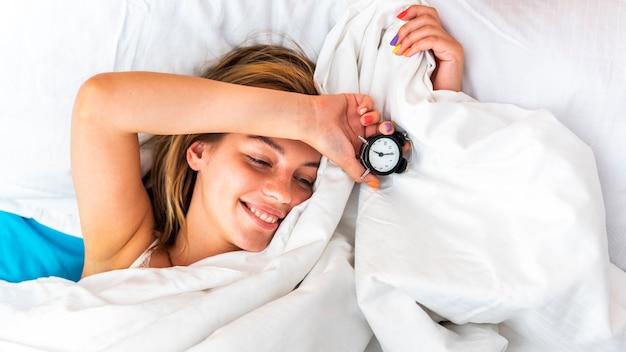 ベッドのシーツの下で時計を保持しているクローズアップの美しい女性
