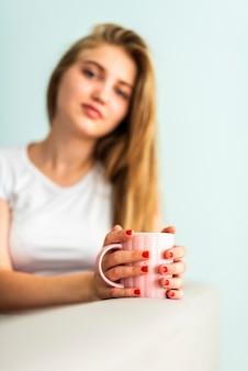 カメラ目線のカップを保持している女性