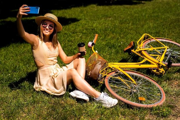 Женщина берет селфи со своим велосипедом