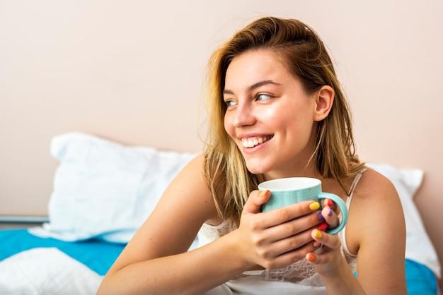 Молодая женщина, глядя в сторону и лежа в постели