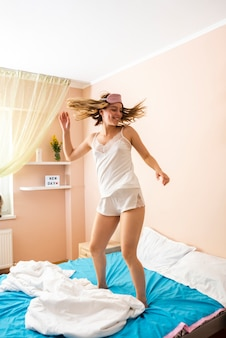 若い女性がベッドでジャンプ