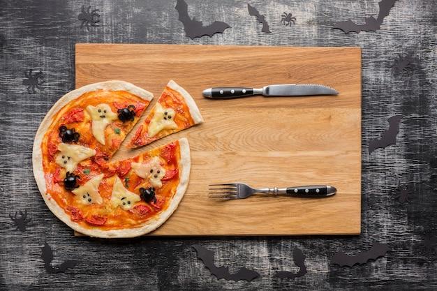 Кусочки пиццы с призраками хэллоуина и столовыми приборами