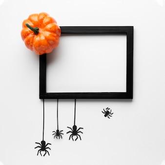 ハロウィーンのカボチャとモックアップフレーム付きクモ