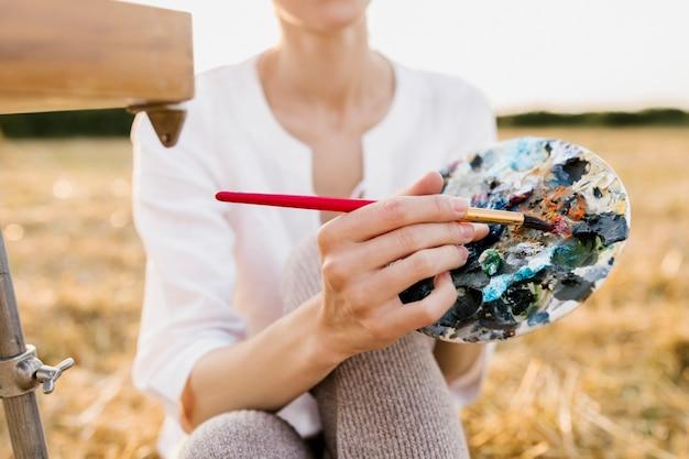 絵画パレットを保持している若い創造的な女性