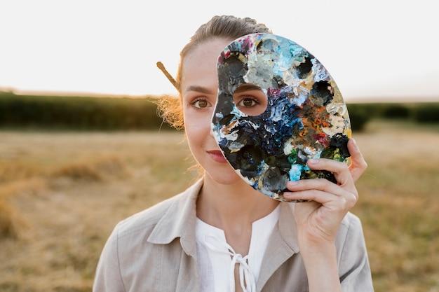 絵画パレットを保持している創造的な若い女性