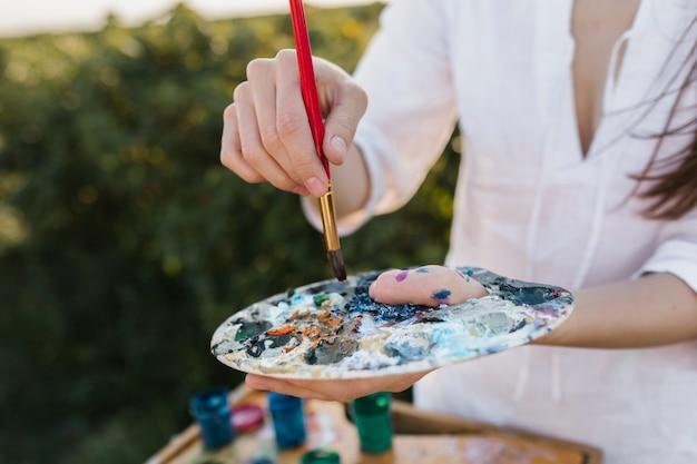 絵画パレットを保持しているクローズアップの女性