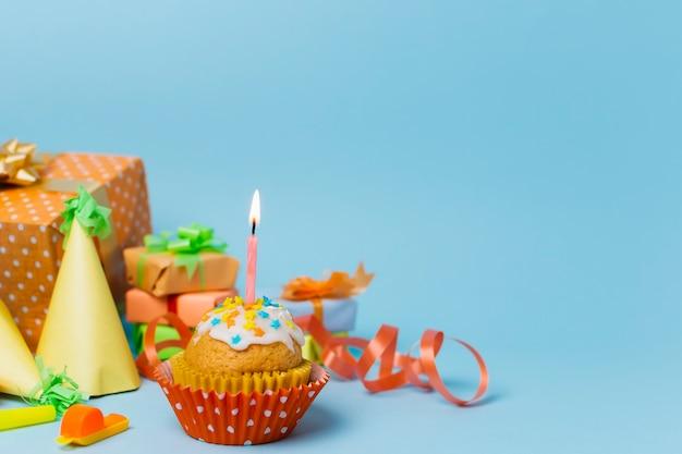 点灯ろうそくと正面の甘いカップケーキ